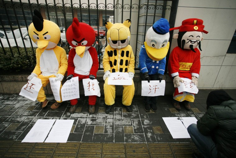 Migrant workers dressed up as Angry Birds (L and 2nd L), Garfield (C), Donald Duck characters and the Chinese God of Wealth (R) during a sit-in protest to demand their salaries outside the China National Radio headquarters in Beijing January 31, 2013. The five migrant workers, whose salaries had been defaulted by various companies after working at several construction sites in Zhangjiakou of Hebei province, came to Beijing in order to raise public awareness and get help, local media reported. The Chinese characters on the papers read, 'Give me back my hard-earned money.' (Stringer/Reuters)