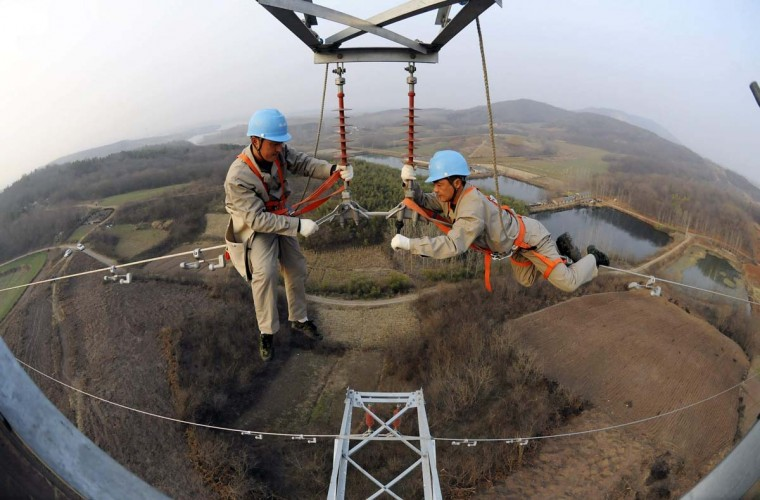 Workers check on electricity pylon situated amid farmlands in Chuzhou, Anhui province, February 5, 2013. A leading think tank of China predicted that China's GDP will grow in 2013 at a rate of 8.4 percent, up by 0.6 percentage points from that of 2012, Xinhua News Agency reported. (China Daily/Reuters)