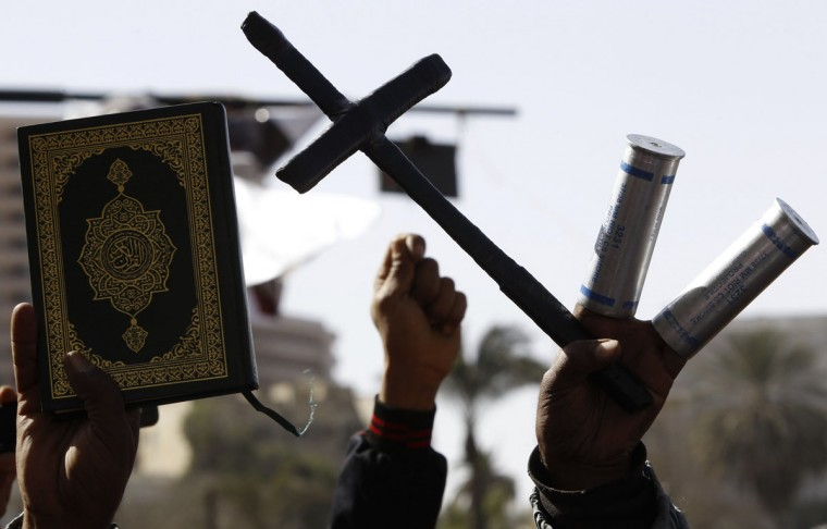 Protesters, who oppose Egyptian President Mohamed Mursi, hold a cross, a Koran and empty tear gas canisters during a demonstration against Mursi and members of the Muslim Brotherhood at Tahrir Square in Cairo. (Amr Abdallah Dalsh/Reuters)