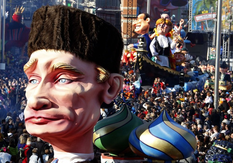 """The float with a giant figure of Russian President Vladimir Putin (L) is paraded through the crowd followed by giant figures of French President Francois Hollande and German Chancellor Angela Merkel during the Carnival parade in Nice. The 129th Carnival of Nice runs from February 15 to March 6 and will celebrate the """"King of the five continents"""". (Eric Gaillard/Reuters)"""