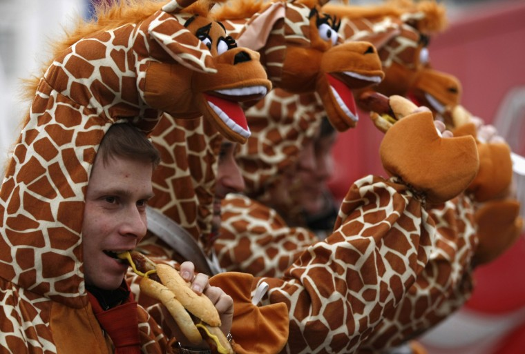 "Men dressed in giraffe costumes eat sausages during ""Weiberfastnacht"" (Women's Carnival) in Cologne February 7, 2013. Women's Carnival marks the start of a week of street festivals, the highlight of the event being ""Rosenmontag"" (Rose Monday), the final day of the carnival where mass processions are held. (Ina Fassbender/Reuters)"