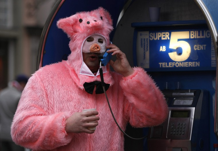 "A man in a pig costume uses a pay phone during ""Weiberfastnacht"" (Women's Carnival) in Cologne February 7, 2013. Women's Carnival marks the start of a week of street festivals, the highlight of the event being ""Rosenmontag"" (Rose Monday), the final day of the carnival where mass processions are held. (Ina Fassbender/Reuters)"