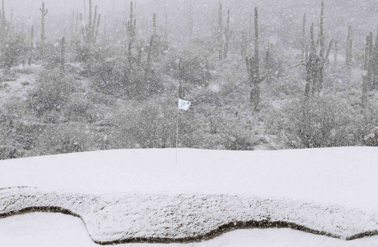 The 18th green is covered in snow as play was suspended during the first round of the WGC-Accenture Match Play Championship golf tournament in Marana, Arizona. Play was suspended at 1807 GMT because of driving rain and snow in the opening round of the WGC-Accenture Match Play Championship on Wednesday. (Matt Sullivan/Reuters)