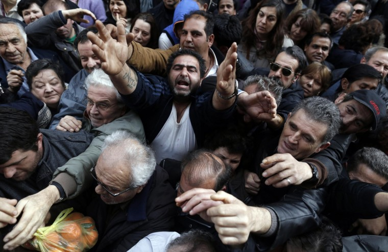 People reach out to take fruits and vegetables freely distributed by farmers during a protest against high production costs outside the Agriculture Ministry in Athens. (John Kolesidis/Reuters)