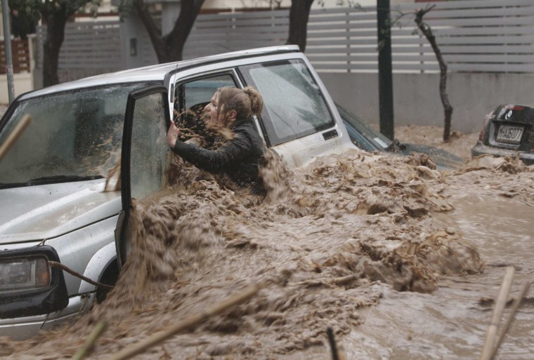 A woman stuck in her car reacts as flood waters gush past her during heavy rain in Chalandri suburb north of Athens, Greece. (John Kolesidis/Reuters)