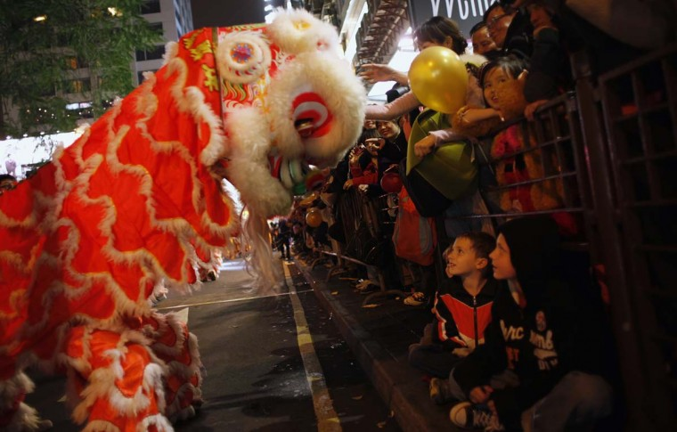 A lion dance troupe performs in front of children during a Chinese New Year evening parade at Hong Kong's Tsim Sha Tsui shopping district February 10, 2013. Participants from 14 countries and regions took part in the parade on Sunday to celebrate the first day of the Year of the Snake, according to the Chinese Zodiac. (Bobby Yip/Reuters)