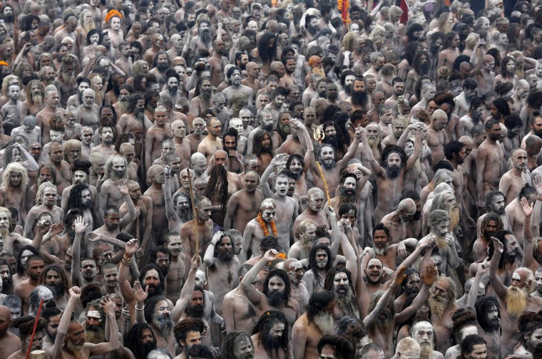 Naga Sadhus or Hindu holy men raise their arms while shouting religious hymns on the banks of the river Ganges after taking the holy dip during the third 'Shahi Snan' (grand bath) at the ongoing 'Kumbh Mela' or Pitcher Festival, in the northern Indian city of Allahabad. During the festival, Hindus take part in a religious gathering on the banks of the river Ganges. The festival is held every 12 years in a temporary city covering an area larger than Athens, spread over a wide sandy river bank in Allahabad at the point where the Ganges and Yamuna rivers meet a third mythical river. (Adnan Abidi/Reuters)