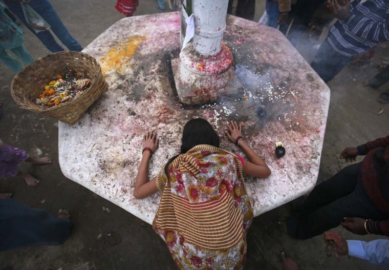 A devotee who is believed to be possessed by evil spirits lies in a state of trance on a sacred platform at Guru Deoji Maharaj temple during a ghost fair at Malajpur village in Betul district in the central Indian state of Madhya Pradesh January 27, 2013. (Danish Siddiqui/Reuters)
