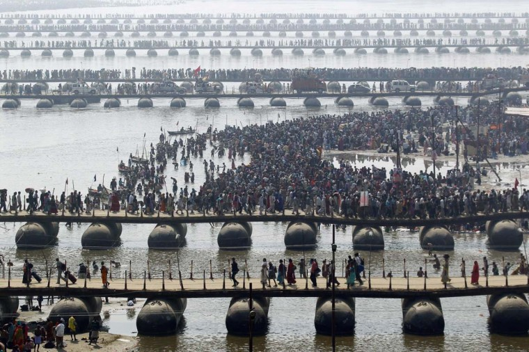 "Hindu devotees cross the river Ganges on pontoon bridges after bathing in the waters at Sangam - the confluence of the Ganges, Yamuna and mythical Saraswati rivers - after the second ""Shahi Snan"" (grand bath), during the ongoing ""Kumbh Mela"" or Pitcher Festival in the northern Indian city of Allahabad February 10, 2013. Hundreds of thousands of pilgrims take a bracing plunge in India's sacred Ganges river to wash away lifetimes of sins, in a an ever-growing religious gathering that is already the world's largest. (Jitendra Prakash/Reuters)"