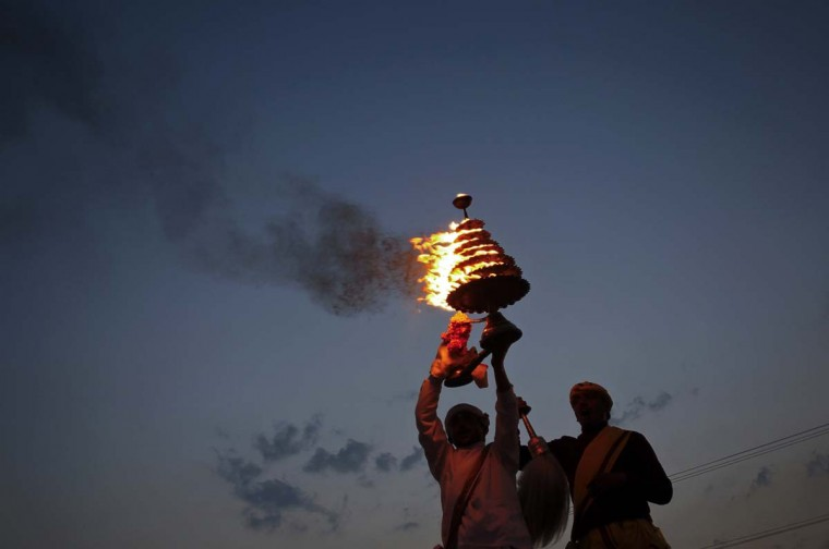 Hindu priests lift up an oil lamp as they perform an evening prayer ceremony for the victims of the explosions which took place in Hyderabad on Thursday, on the banks of the river Ganges in the northern Indian city of Allahabad February 24, 2013. (Jitendra Prakash/Reuters)