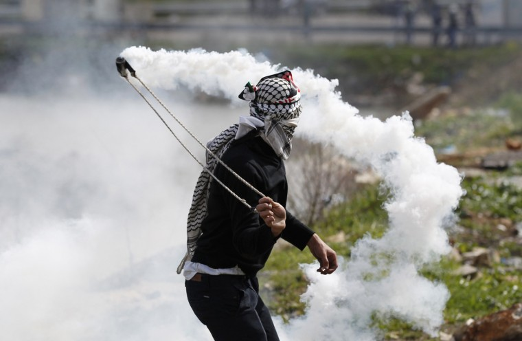 A Palestinian uses a sling to throw a teargas canister fired by Israeli troops during clashes outside Israel's Ofer military prison near the West Bank city of Ramallah. Hundreds of Palestinian prisoners in Israeli jails declared a one-day fast on Tuesday in solidarity with four inmates whose hunger strike has fuelled violent anti-Israeli protests outside the prison and in West Bank towns. (Darren Whiteside/Reuters)
