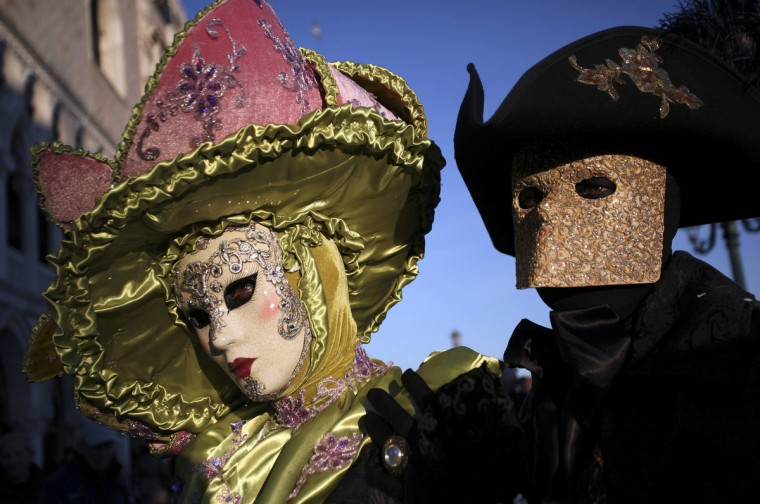 Two masked revelers pose in Saint Mark's Square during the Venetian Carnival in Venice February 3, 2013. (Manuel Silvestri/Reuters)