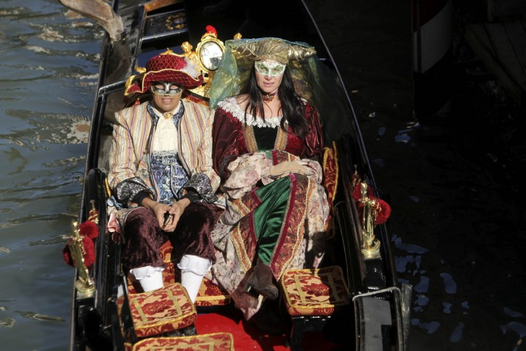 A couple dressed in traditional costumes sits in a gondola boat during the Venetian Carnival in Venice February 3, 2013. (Manuel Silvestri/Reuters)