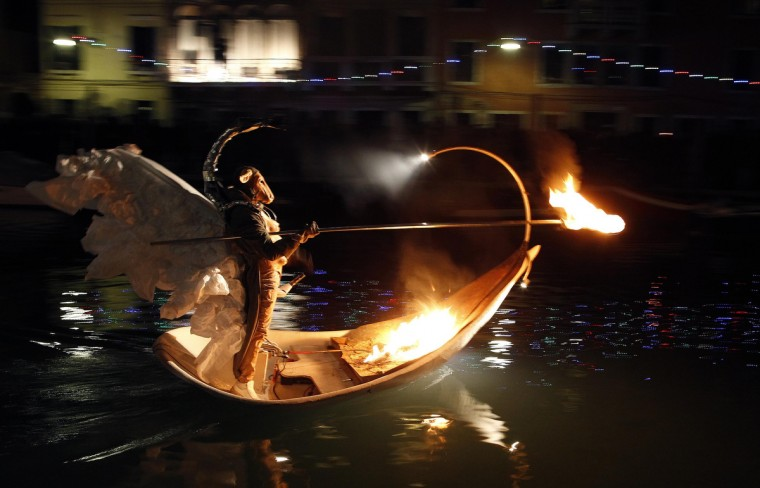 "An artist from the French performance group called Ilotopie performs in an aquatic show ""MetaMorPhosiS Aquaticae"" on the Cannaregio Canal during a parade as part of the opening ceremony of the Venice carnival January 26, 2013. (Alessandro Bianchi/Reuters)"