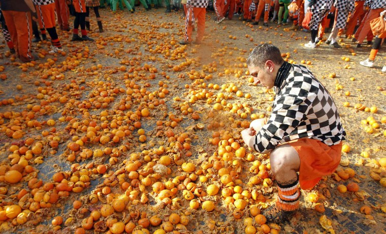 A member of a rival team collects oranges in the middle of the square during an annual carnival battle in the northern Italian town of Ivrea February 10, 2013. Dressed up as Middle Age kings' guards, a group of men ride in a horse-drawn carriage and pelt 'foot soldiers' with oranges as thousands of people gather to re-enact a Middle Age battle when the townsfolk of Ivrea overthrew an evil king. In a strange twist, instead of swords and cross bows, these days the weapons of choice are oranges. (Stefano Rellandini/Reuters)