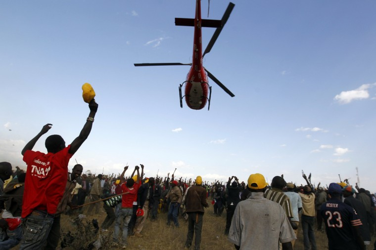 Supporters of Kenya's Deputy Prime Minister and presidential candidate Uhuru Kenyatta cheer as he leaves on a helicopter after a campaign rally in the Rift Valley town of Suswa, about 70 km (43 miles) west of the capital Nairobi. The trial of Kenyan presidential candidate Kenyatta for crimes against humanity is unlikely to begin until August, international prosecutors said on Tuesday, a delay that would leave him freer to run in the election's second round. Kenya will hold its general elections on March 4. (Thomas Mukoya/Reuters)