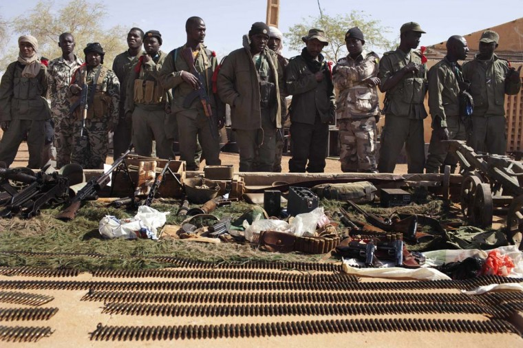 Malian soldiers look at munitions on display for the press at the Malian airbase where French soldiers are stationed in Gao February 24, 2013. Malian and French army officers said the munitions were captured from radical Islamist groups over the past weeks. (Joe Penney/Reuters)