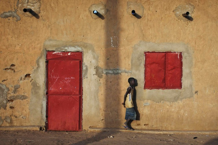 A boy walks past metal doors and windows on a house in Gao. (Joe Penney/Reuters)