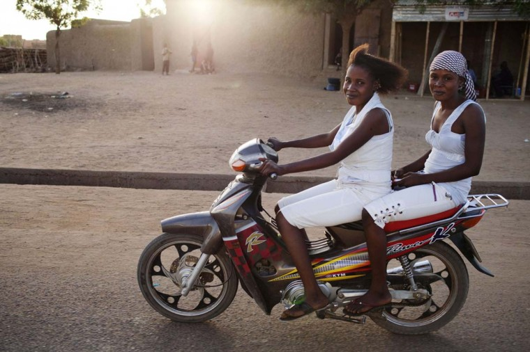 Girls ride a motorcycle at sunset in Gao February 23, 2013. (Joe Penney/Reuters)