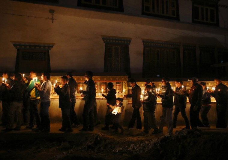 Tibetans hold lit candles as they walk around the Tibetan monastery during a candlelight vigil to show solidarity to Tibetans who have self-immolated, and to mark the 100th anniversary of the 1913 Tibetan Proclamation of Independence, at the Tibetan Refugee Camp in Lalitpur. A Tibetan monk self-immolated on Wednesday at the premises of the Boudhanath Stupa in Kathmandu.(Navesh Chitrakar/Reuters)