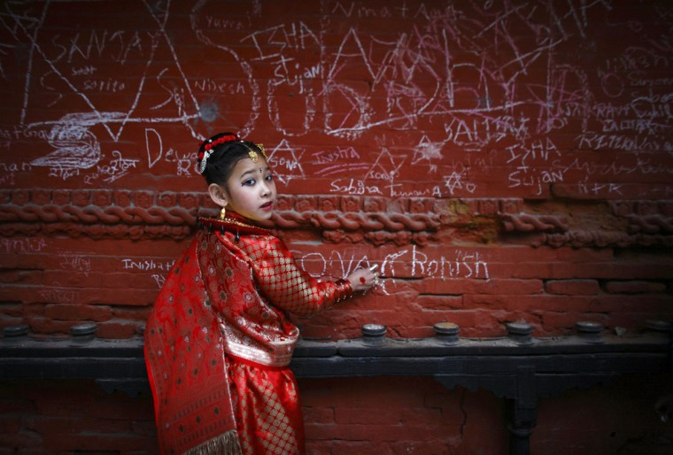 Sona Nakarmi, 7, writes on a wall at the Saraswati temple during the Shreepanchami festival in Kathmandu. Children are given their first writing and reading lessons at the temple during this festival in the belief that the goddess of education Saraswati will help them excel in education. (Navesh Chitrakar/Reuters)