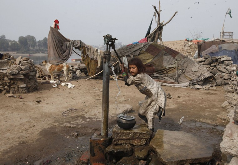 A girl uses a water pump to fill her pot on the outskirts of Lahore, Pakistan. (Mohsin Raza/Reuters)