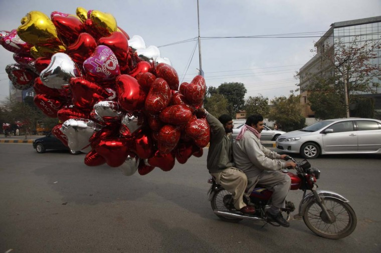 A man holds heart-shaped balloons while riding on a motorcycle along a road on Valentine's Day in Lahore February 14, 2013. (Mohsin Raza/Reuters)