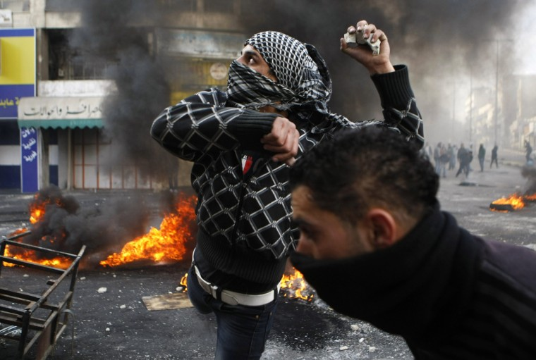 A Palestinian protester throws stones during clashes with Israeli soldiers in the West Bank city of Hebron following the funeral of Palestinian prisoner Arafat Jaradat. Jaradat's death in an Israeli jail on Saturday and a hunger strike by four other Palestinian inmates have raised tension in the occupied territory after repeated clashes between stone-throwers and Israeli soldiers in recent days. (Mussa Qawasma/Reuters)