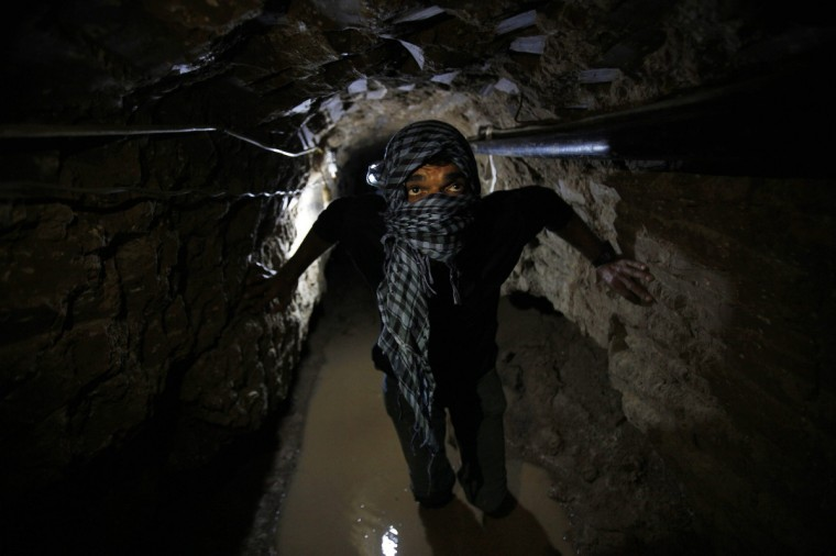 A Palestinian works inside a smuggling tunnel flooded by Egyptian forces, beneath the Egyptian-Gaza border in Rafah, in the southern Gaza Strip. Egypt will not tolerate a two-way flow of smuggled arms with the Gaza Strip that is destabilising its Sinai peninsula, a senior aide to its Islamist president said, explaining why Egyptian forces flooded sub-border tunnels last week. T(Ibraheem Abu Mustafa/Reuters)