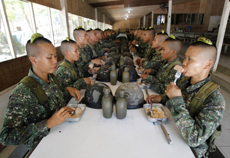 Newly recruited female marines take their lunch with fellow soldiers after undergoing drills inside the marine headquarters in the town of Ternate, Cavite city, south of Manila. There are an estimated 350 women combatants in the 10,000-member Philippine marines who go through the same rigid physical and mental training as their men counterparts. Since 2006, female marine officers of the Marine Corps have been performing in the field of assault armor, field artillery, airborne and other combat duties, a marine officer said. (Romeo Ranoco/Reuters)