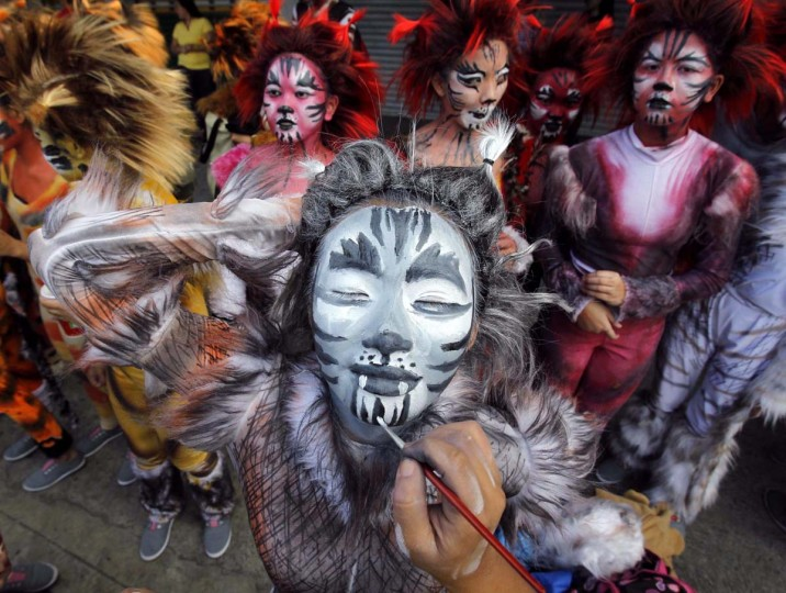 """A student has her face painted as part of her nature-inspired costume before participating in a parade for the Caracol festival in Makati city, metro Manila February 24, 2013. The annual Caracol festival, the """"Mardi Gras of Makati"""", is held as a tribute to mother nature. (Romeo Ranoco/Reuters)"""