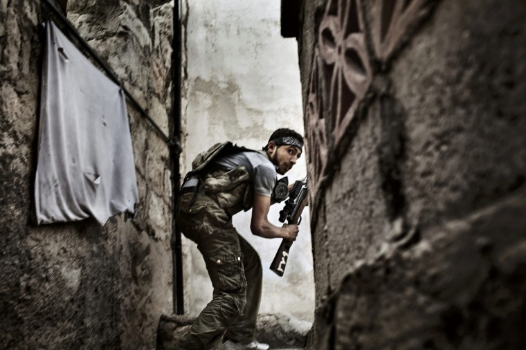 #3: Fabio Bucciarelli of Italy, a photographer working for the Agence France-Presse, has won the second prize in the Spot News Stories category of the World Press Photo Contest 2013 with the series 'Battle to death.' The picture shows a Free Syrian Army fighter taking up a position during clashes against government forces in the Sulemain Halabi district. in Aleppo, taken on October 10, 2012 and distributed by the World Press Photo Foundation February 15, 2013. (Fabio Bucciarelli/Agence France-Presse/World Press Photo/Handout/Reuters)