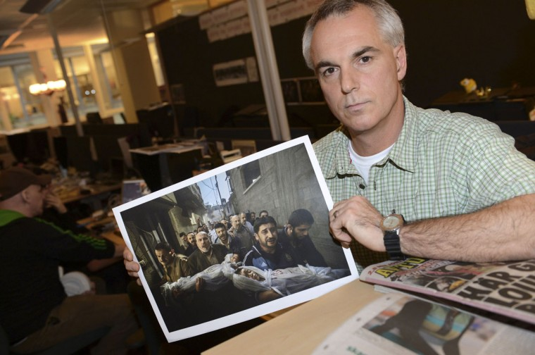 Paul Hansen of Sweden, a photographer working for the Swedish daily Dagens Nyheter, poses holding his picture that won the World Press Photo of the year for 2012, at Dagens Nyheter's office in Stockholm February 15, 2013. The photograph, which Hansen took on November 20, 2012, shows a group of men carrying the bodies of two dead children, who were killed in an Israeli missile strike on Gaza City, and won the top World Press Photo prize on Friday. (Fredrik Sandberg/Scanpix/Reuters)