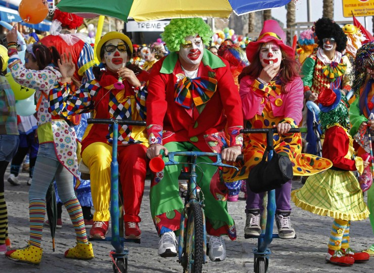 Carnival revellers dressed as clowns pedal on the clowns parade in Sesimbra village February 11, 2013. (Jose Manuel Ribeiro /Reuters)