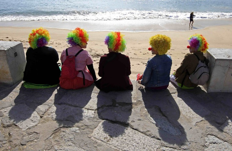 Carnival revellers dressed as clowns sit at the village beach before the clowns parade in Sesimbra February 11, 2013. (Jose Manuel Ribeiro /Reuters)