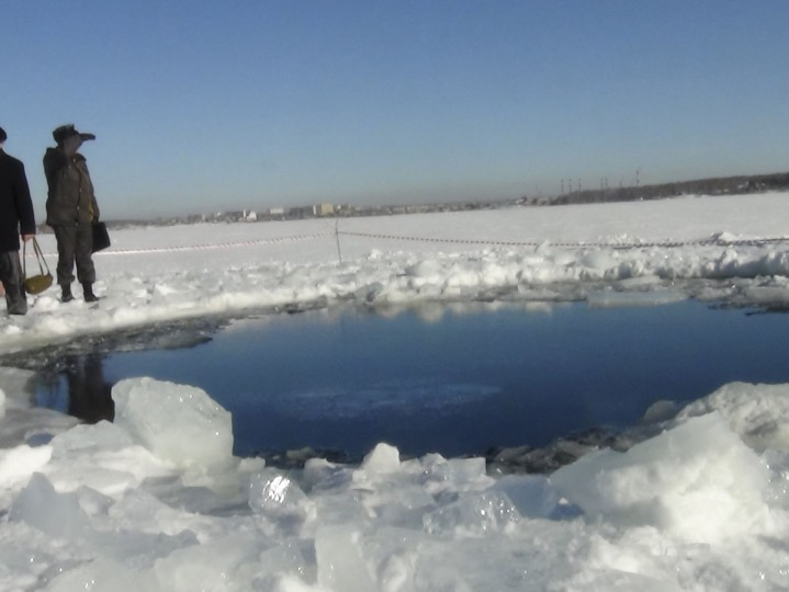 Russian police work near an ice hole, said by the Interior Ministry department for Chelyabinsk region to be the point of impact of a meteor seen earlier in the Urals region, at Lake Chebarkul some 50 miles west of Chelyabinsk, Russia. (Photo provided by Chelyabinsk region Interior Ministry / Reuters)
