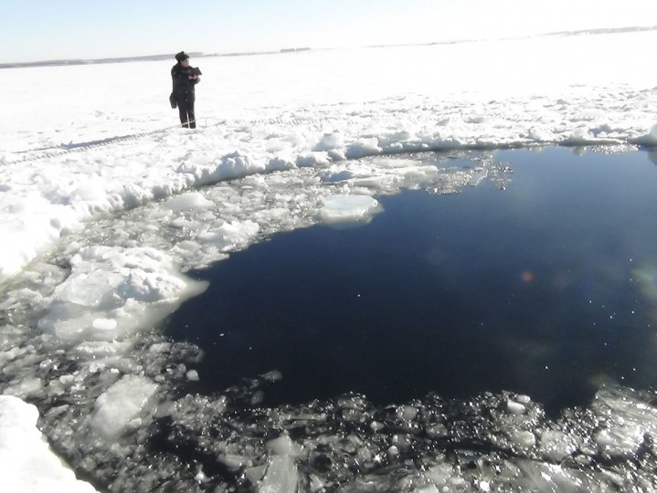 A Russian policeman works near an ice hole, said by the Interior Ministry department for Chelyabinsk region to be the point of impact of a meteor seen earlier in the Urals region, at Lake Chebarkul some 50 miles west of Chelyabinsk, Russia. (Photo provided by Chelyabinsk region Interior Ministry / Reuters)