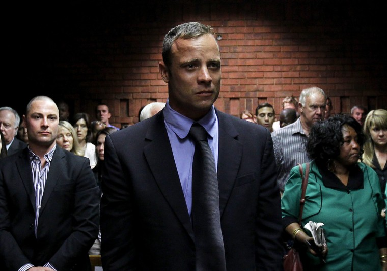 Oscar Pistorius awaits the start of court proceedings while his brother Carl (L) looks on, in the Pretoria Magistrates court. Pistorius, a double amputee who became one of the biggest names in world athletics, was applying for bail after being charged in court with shooting dead his girlfriend, 30-year-old model Reeva Steenkamp, in his Pretoria house. (Siphiwe Sibeko/Reuters)