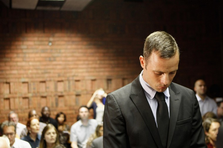 """Oscar Pistorius stands in the dock during a break in court proceedings at the Pretoria Magistrates court. """"Blade Runner"""" Pistorius, a double amputee who became one of the biggest names in world athletics, was applying for bail after being charged in court with shooting dead his girlfriend, 30-year-old model Reeva Steenkamp, in his Pretoria house. (Siphiwe Sibeko/Reuters)"""