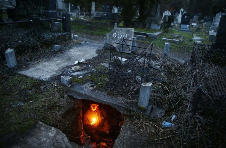 Bratislav Stojanovic, a homeless man, holds candles as sits in a tomb where he lives in southern Serbian town of Nis . Stojanovic, 43, a Nis-born construction worker never had a regular job. He first lived in abandoned houses, but about 15 years ago he settled in the old city cemetery. (Marko Djurica/Reuters)