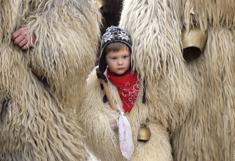 "A boy dressed in sheep skin stands between his mother and father as they observe festivities during the annual carnival, held to mark the end of winter, in Litija January 7, 2013. During the carnival, people dress up as the ""Kurent"", a fluffy but demon-like creature that banishes the winter and heralds the arrival of spring with loud noise and dancing. (Srdjan Zivulovic/Reuters)"