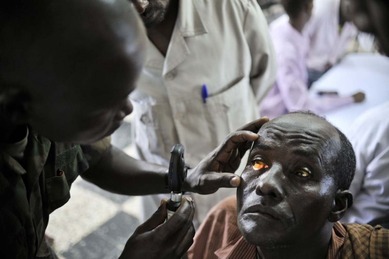 An army medic checks a patient's eyes at a medical outreach centre in Mogadishu, February 5, 2013. As part of the Tarehe Sita celebrations, which commemorates the takeover of power in 1986 by the NRM government in Uganda, the Ugandan People's Defence Force (UPDF) provided three days of medical outreach services in Mogadishu to act as a symbolic gesture of the relationship Uganda has with the people of Somalia. (Tobin Jones/Handout via Reuters)