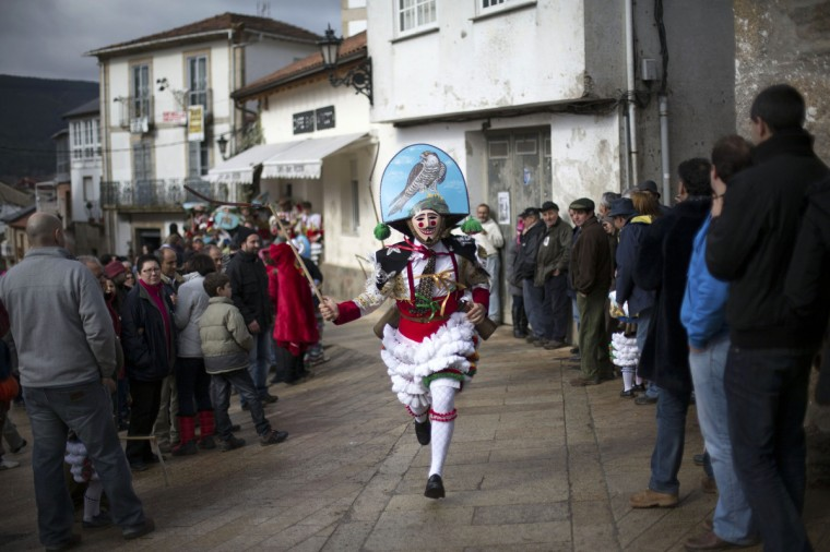 "Carnival revellers dressed as ""Peliqueiros"" run through a street in Spain's northwestern village of Laza February 12, 2013. ""Peliqueiros"", or ancient tax collectors, pursued villagers through the streets ringing their cowbells and hitting villagers with their sticks. (Miguel Vidal/Reuters)"