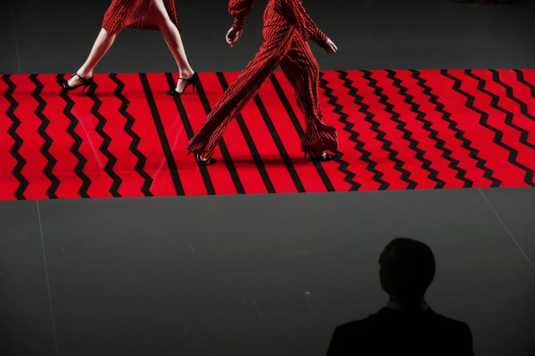 A man looks at models presenting creations from Ailanto's Fall/Winter 2013 collection during the Mercedes-Benz Fashion Week in Madrid. (Susana Vera/Reuters)