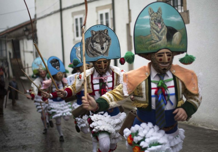 "Carnival revellers dressed as ""Peliqueiros"" run through a street in Spain's northwestern village of Laza February 10, 2013. ""Peliqueiros"" or ancient tax collectors, pursued villagers through the streets ringing their cowbells and hitting villagers with their sticks. (Miguel Vidal/Reuters)"