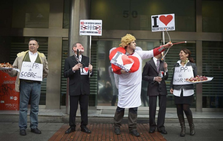 "Protesters wearing masks depicting Spain's Prime Minister Mariano Rajoy (2nd L) and Basque premier Inigo Urkullu (2nd R) carry scissors, beside a man dressed as Cupid during a Valentine's Day themed demonstration against central and Basque regional government cuts in Bilbao February 14, 2013. Stickers on protesters coats read, ""I love Social cuts"". (Vincent West/Reuters)"