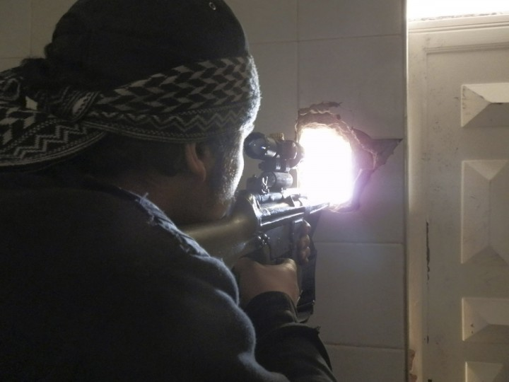 A member of the Free Syrian Army points his weapon through a hole in a wall as he takes up a defense position in Daraya. (Fadi Al-Derani/Reuters)