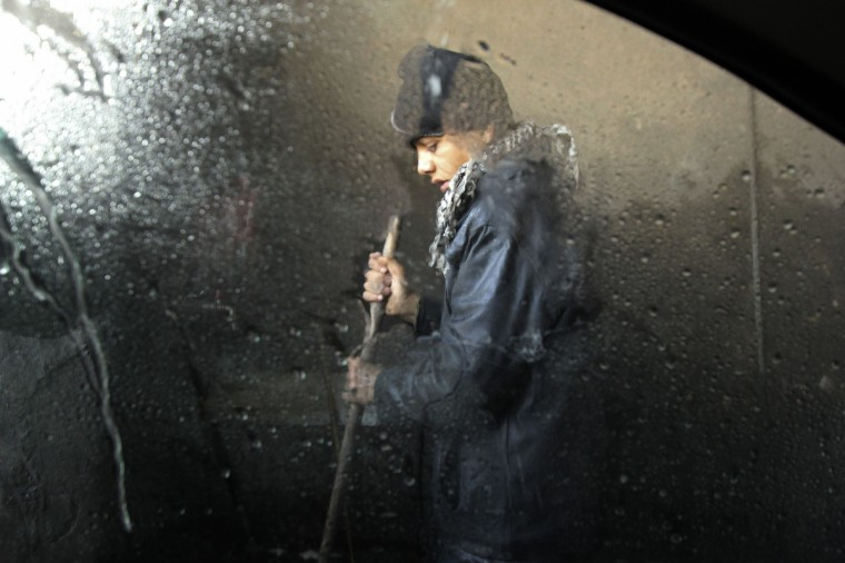 A boy works at a car wash in Aleppo. (Giath Taha/Reuters)