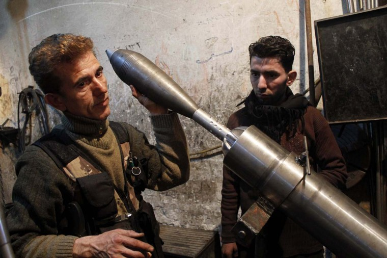 A Free Syrian Army fighter holds an improvised mortar shell inside a factory which previously manufactured steel and iron in Aleppo February 18, 2013. (Hamid Khatib/Reuters)