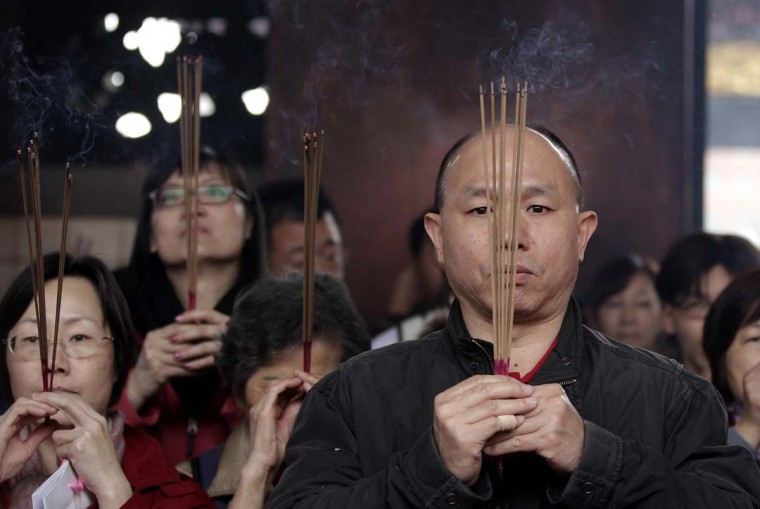 Worshippers holding incense sticks pray during Chinese Lunar New Year celebrations at the Lungshan temple in Taipei February 10, 2013. The Lunar New Year, also known as the Spring Festival, begins on February 10 and marks the start of the Year of the Snake, according to the Chinese zodiac. (Pichi Chuang/Reuters)